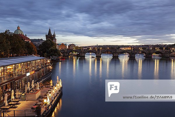 Evening on Vltava river in Prague  Czechia. Charles Bridge in the distance.