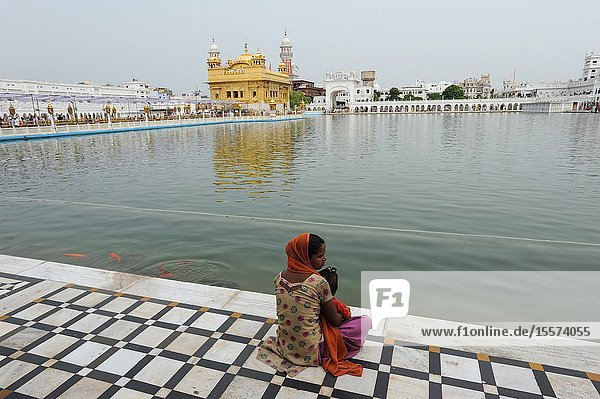 Amritsar  Punjab  India - Female Sikh devotee with children at the Amrit Sarover (sacred pool) of the Golden Temple sanctuary  the holiest place of worship for Sikhs.