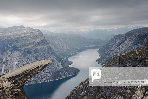 View of Trolltunga cliff and lake between mountains  picturesque landscape  beauty in nature  paradise on Earth  sunny day  Odda  Norway. cloudy day.