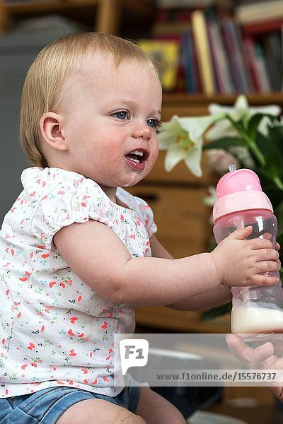Child drinking milk from bottle  adorable and cute baby portrait.