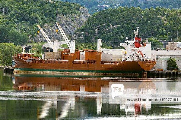 Cargo ship loading paper at paper mill at Corner Brook Newfoundland Canada.