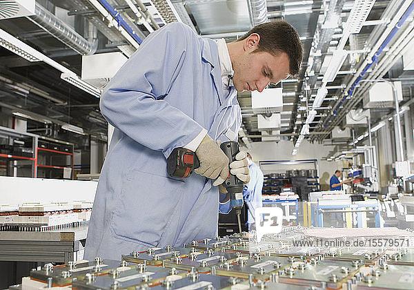 Deutschland  Nürnberg  Junger Mann arbeitet in Fabrik