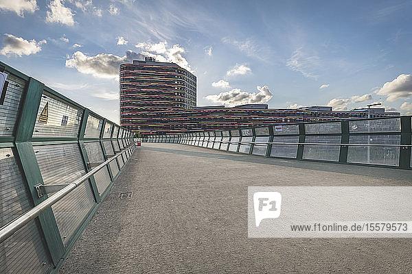 Diminishing perspective of footbridge leading towards office building against sky in Hamburg  Germany