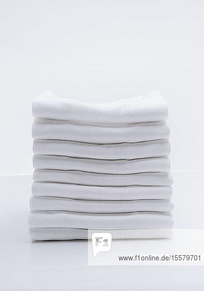 Stapel von weißen Hemden auf weißem Hintergrund