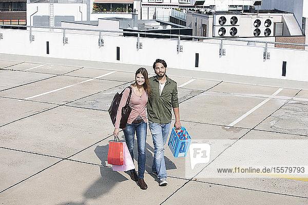 Deutschland  Köln  Junges Paar mit Einkaufstaschen  lächelnd