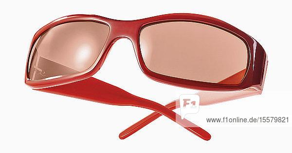 Rote Sonnenbrille vor weißem Hintergrund  Nahaufnahme