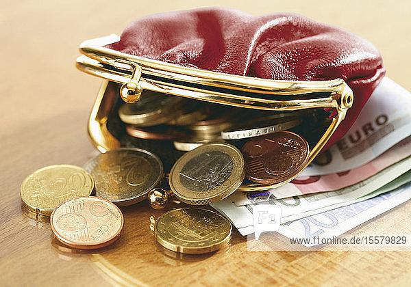 Nahaufnahme von Euro-Banknoten und auslaufenden Münzen im Portemonnaie