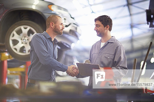 Automechaniker und Kunde schütteln Hände in Reparaturwerkstatt