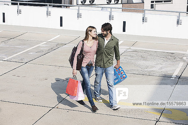 Germany  Cologne  Young couple with shopping bags  smiling