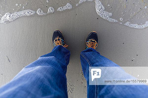 Beine und Füße des Menschen an der Meeresküste