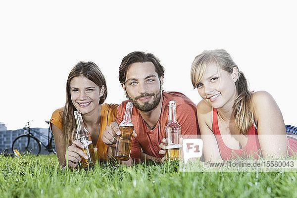 Deutschland  Köln  Junger Mann und Frau im Gras liegend mit Bierflaschen  lächelnd  Porträt