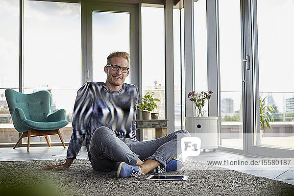 Portrait of smiling young man sitting on carpet with tablet at home