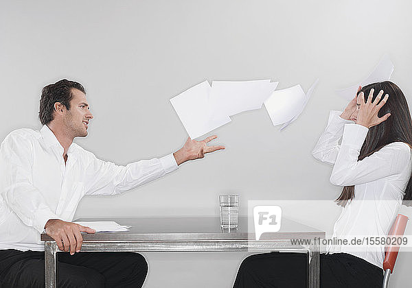 Geschäftsmann wirft Papiere mit einer Frau mit dem Kopf in der Hand