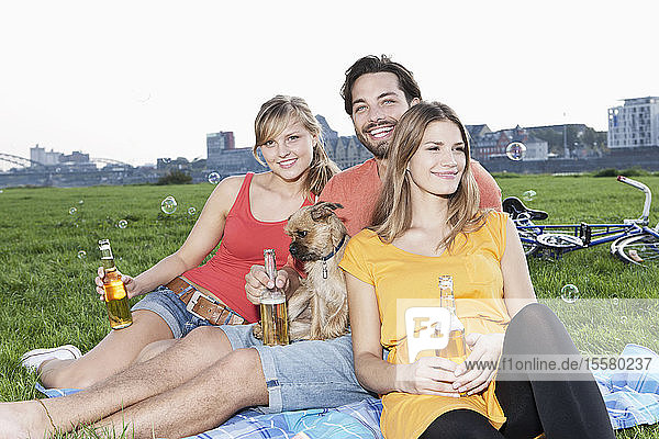 Germany  Cologne  Young man and woman with dog and beer bottle in grass  smiling