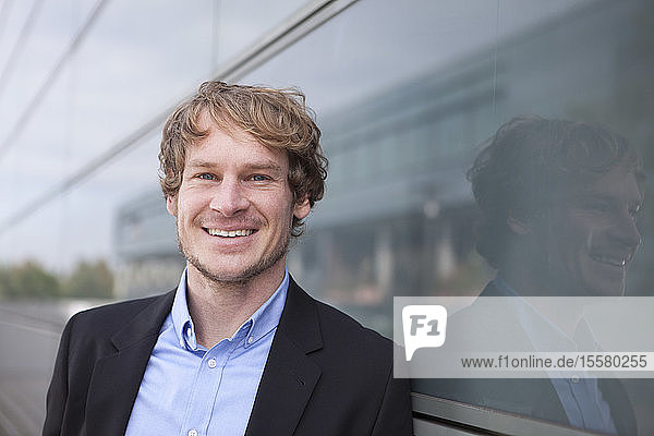 Portrait of smiling businessman in front of glass facade