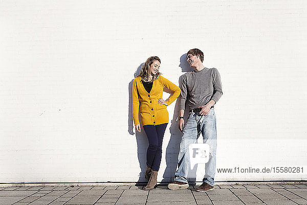 Germany  Bavaria  Munich  Young couple standing against wall  smiling