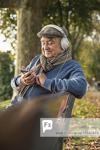 Älterer Mann auf Parkbank mit Handy und Kopfhörern