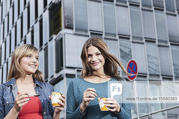 Deutschland  Köln  Junge Frau mit Eisbecher  lächelnd