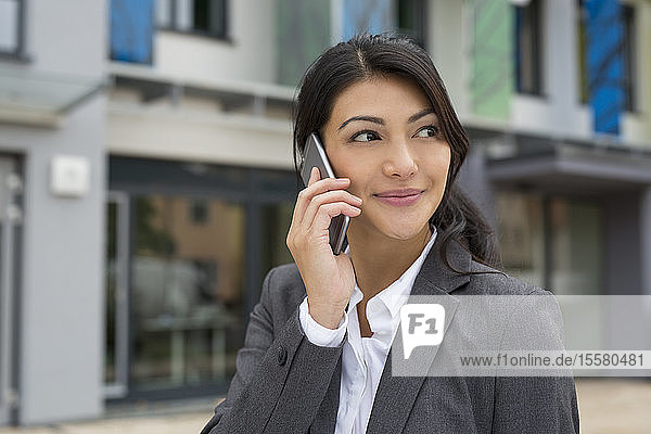 Portrait of smiling businesswoman telephoning with smartphone
