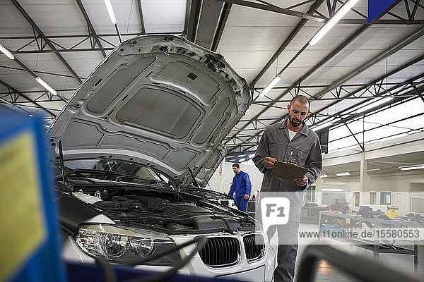 Automechaniker mit Klemmbrett in der Reparaturwerkstatt