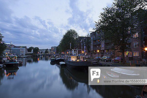 Netherlands  Amsterdam  view to boats at town canal and multi-family house in the background
