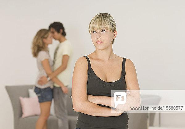 Junge Frau  die mit einem Paar im Hintergrund wegschaut