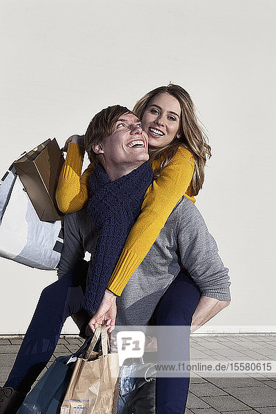 Germany  Bavaria  Munich  Young man carrying woman on his back while she holds shopping bags