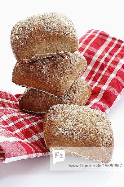 Brotstapel mit Küchentuch auf weißem Hintergrund