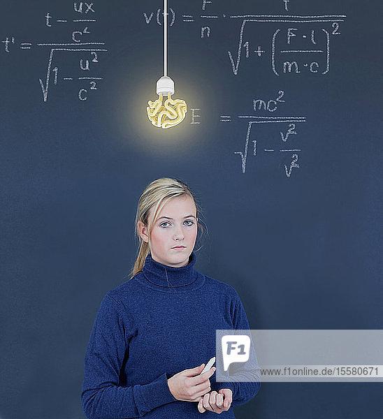 Schulmädchen vor Tafel mit Formel