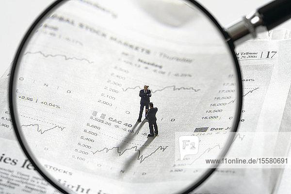 Zwei Figuren auf Zeitungspapierzitaten mit Vergrößerungslinse im Vordergrund