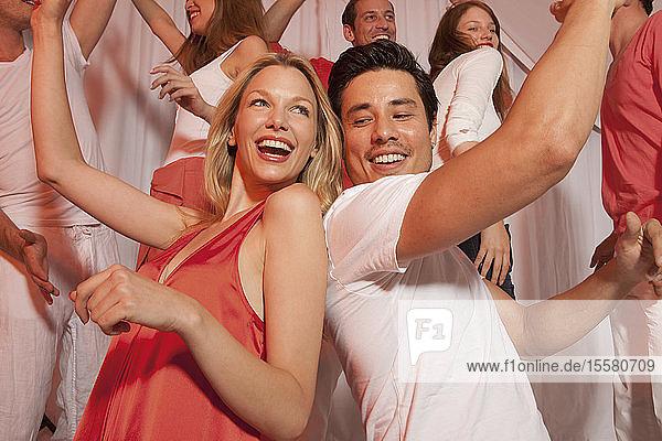 Deutschland  Stuttgart  Gruppe von Menschen  die in einem Nachtclub tanzen  lächelnd