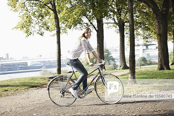 Deutschland  Köln  Junge Frau auf Fahrrad  lächelnd  Portrait