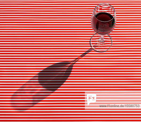 Hochwinkelansicht eines Rotweins  der auf einem gestreiften Tisch serviert wird