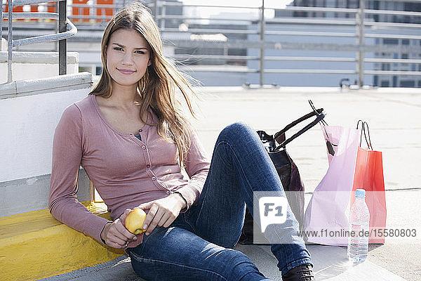 Deutschland  Köln  Junge Frau mit Einkaufstaschen  lächelnd  Portrait