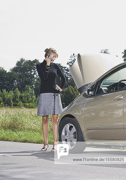 Germany  Augsburg  Young woman standng by car on road using mobile phone
