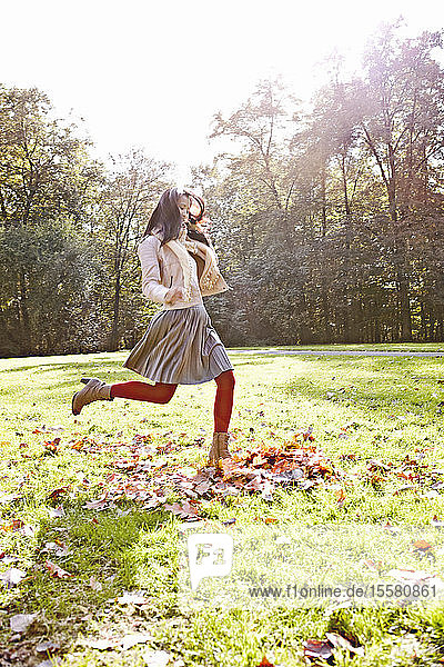 Deutschland  Köln  Junge Frau spielt im Park mit Blättern