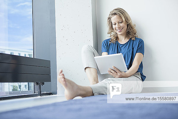 Portrait of smiling mature woman sitting with digital tablet on the floor in her apartment