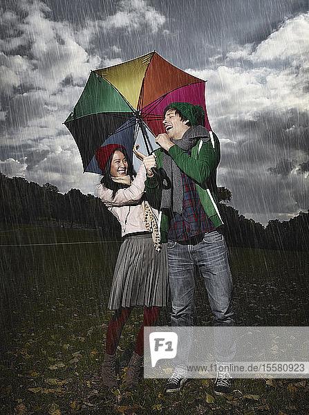 Deutschland,  Köln,  Junges Paar mit Regenschirm im Park,  lächelnd
