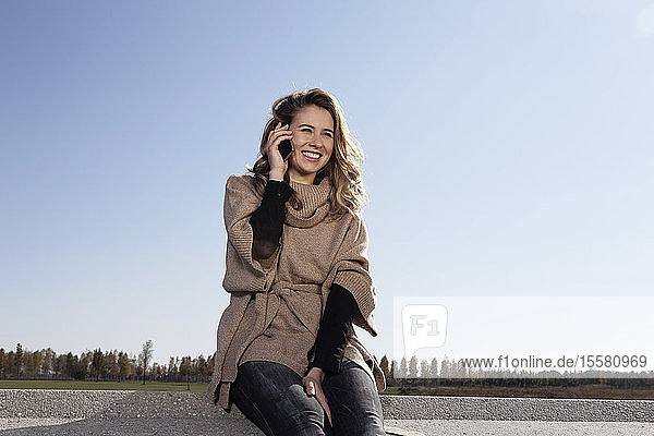 Germany  Bavaria  Munich  Young woman on cell phone  smiling