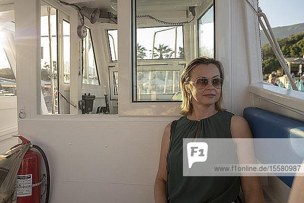 Frau mit Sonnenbrille sitzt auf einem Boot