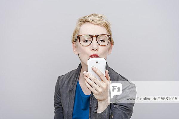 Blonde Frau mit Schmollmund  die sich mit ihrem Smartphone ein Selfie nimmt