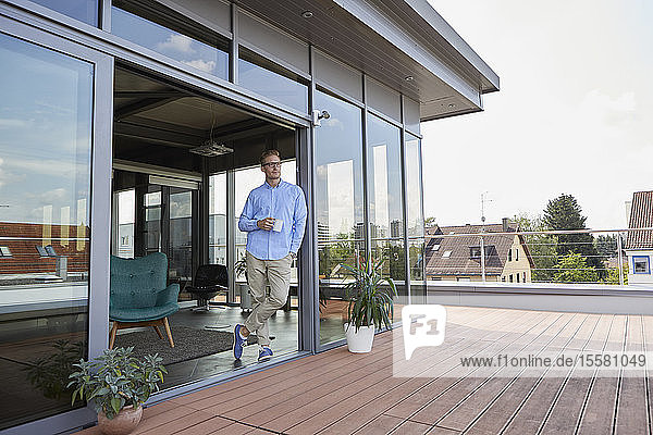Young man with cup of coffee standing at balcony door