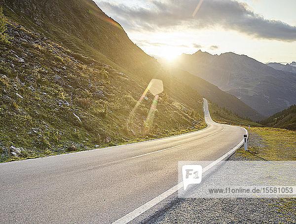 Straße  die bei Sonnenuntergang durch Berge gegen den Himmel führt  Bundesland Tirol  Österreich