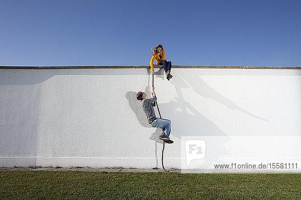 Germany  Bavaria  Munich  Young couple climbing wall
