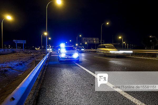 Beleuchtetes Polizeiauto auf der Straße von Madrid in der Nacht