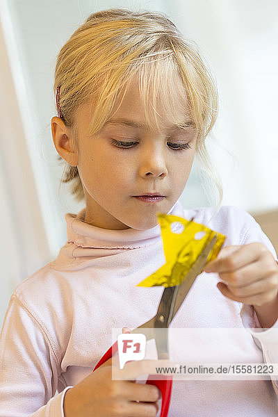Little girl tinkering with scissors and paper