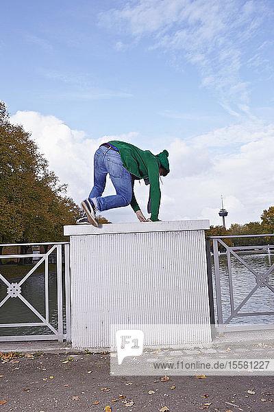Deutschland  Köln  Junger Mann klettert auf Brückengeländer