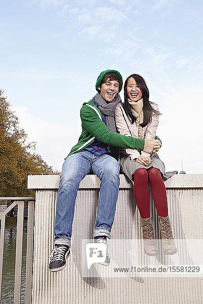 Deutschland  Köln  Junges Paar auf der Brücke sitzend  lächelnd  Porträt