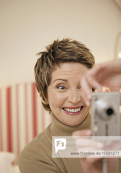 Reife Frau beim Selbstfotografieren mit Digitalkamera