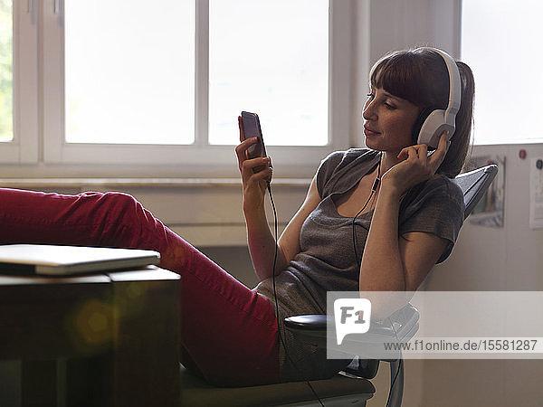 Frau mit Füßen auf dem Tisch und Kopfhörern